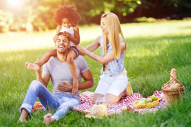 cheerful happy family picnicking - kinder picknick spiele stock-fotos und bilder