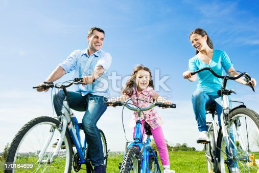 665192886 istock photo Cheerful happy family riding bicycles in the park. 170164699