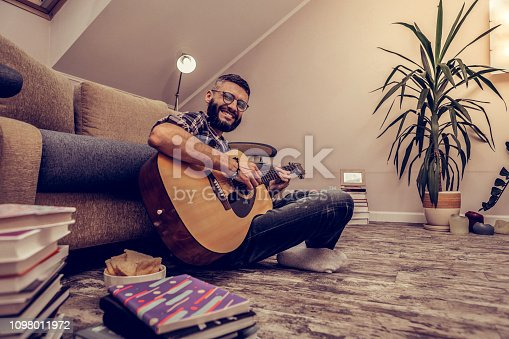 istock Cheerful happy man sitting with his guitar 1098011972