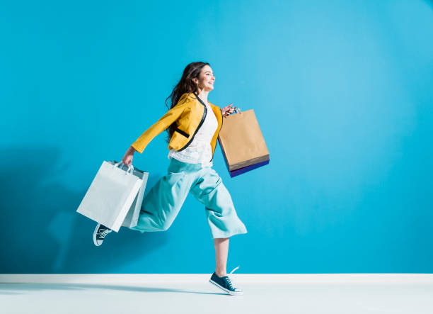 Cheerful happy woman enjoying shopping Cheerful happy woman enjoying shopping: she is carrying shopping bags and running to get the latest offers at the shopping center buying stock pictures, royalty-free photos & images