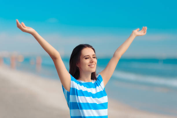 Cheerful Happy Woman Reaching her Arms Up at the Beach stock photo