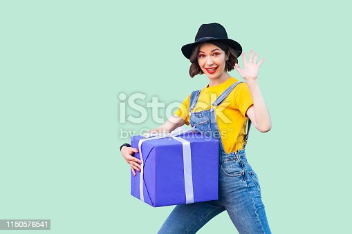 istock Cheerful happy young girl in hipster wear in denim overalls and black hat standing and trying to hold giant big heavy gift box and greeting you, showing five. 1150576541