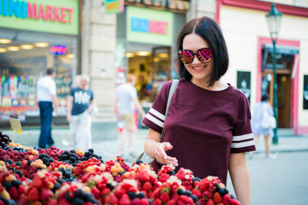 Cheerful happy young woman buying berries on a street market stock photo