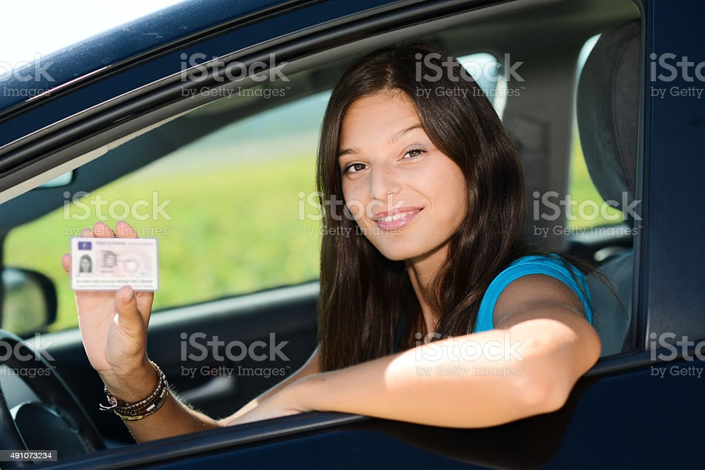 cheerful happy young woman in car showing new driving license stock photo