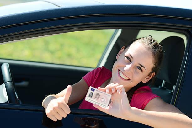 fröhlich glückliche junge frau im auto mit neuer führerschein - führerschein stock-fotos und bilder