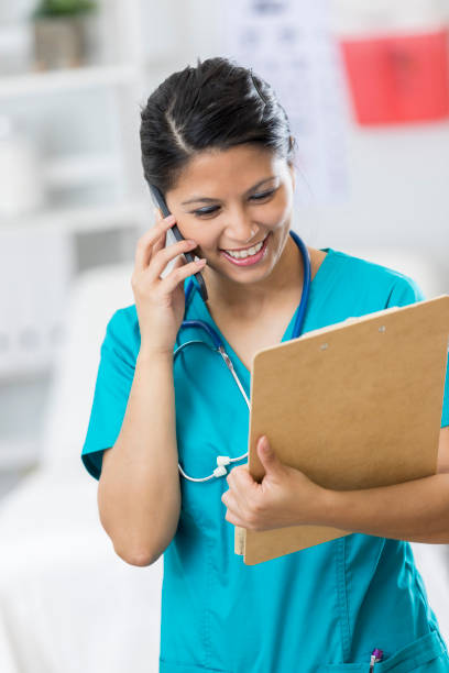 cheerful healthcare professional uses smartphone - nurse on phone stock photos and pictures