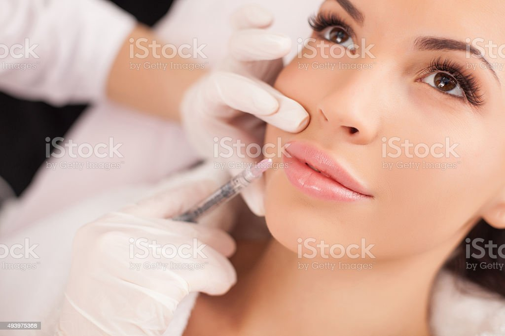 Cheerful healthy lady is visiting expert beautician stock photo