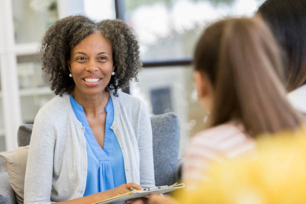 cheerful high school guidance counselor talking with students - school counselor stock pictures, royalty-free photos & images