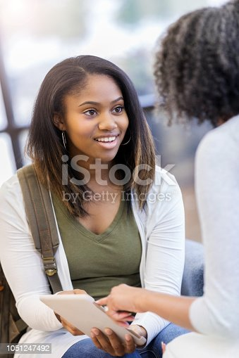 A cheerful teenage girl sits in her living room with her unrecognizable mother and receives a digital tablet as a gift.