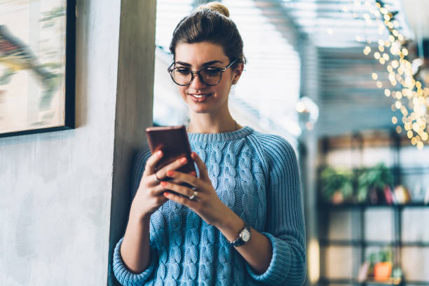 Cheerful hipster blogger in eyeglasses reading funny comments under internet post holding modern smartphone in hands.Positive young woman laughing during online chat with friends on cellular stock photo