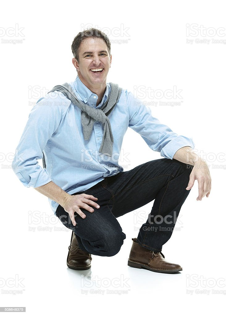 Cheerful hipster crouching & looking at camera stock photo