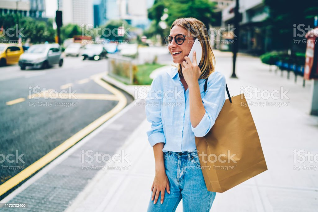 Cheerful hipster girl enjoying walking in downtown having phone...