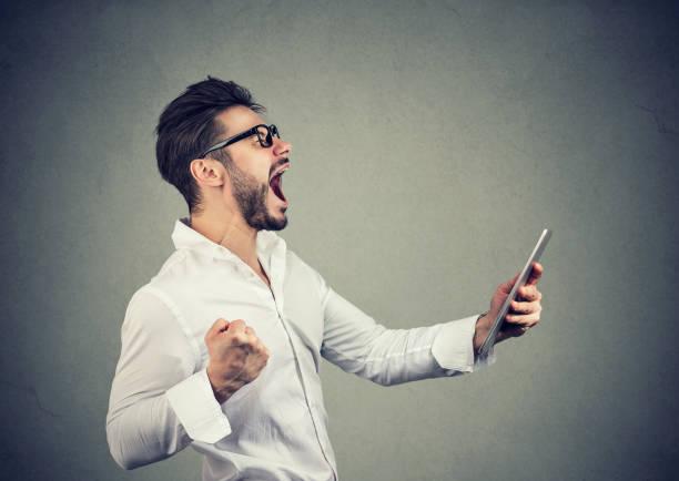 fröhliche hipster mann hält tablet und faust beim schreien vor glück - die besten apps stock-fotos und bilder