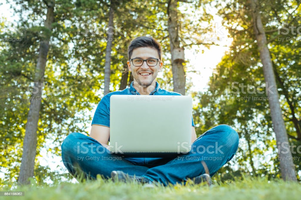 Cheerful hipster man with laptop sitting outdoors in nature. Freedom concept royalty-free stock photo