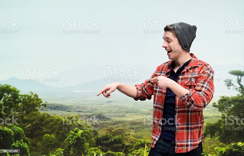 Cheerful hipster on mountain and pointing stock photo