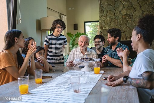 1196170672istockphoto Cheerful Hispanic family surprising grandfather with birthday cake for his birthday 1204468117