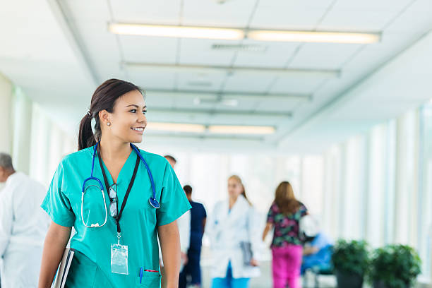 cheerful hispanic nurse walks in hospital corridor - clinica medica foto e immagini stock