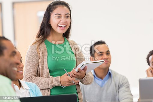 istock Cheerful Hispanic woman asks question during college class 610647662