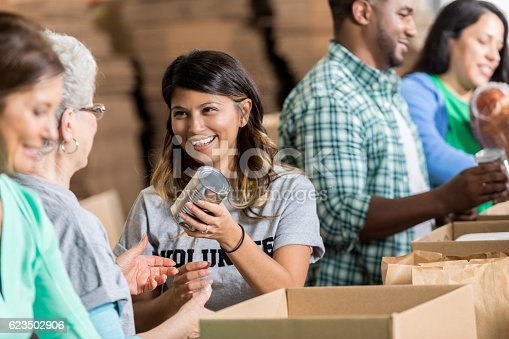 istock Cheerful Hispanic woman volunteers at food bank 623502906
