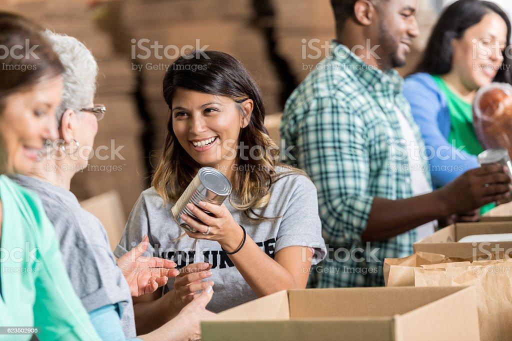Cheerful Hispanic woman volunteers at food bank stock photo