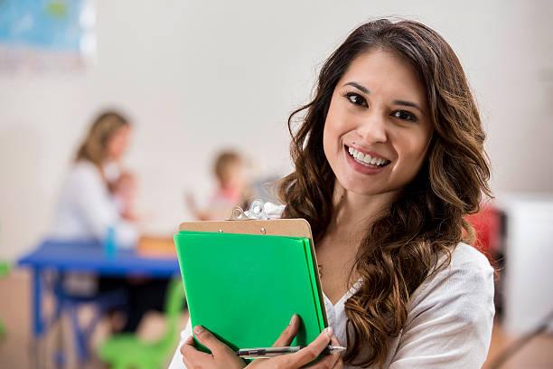 cheerful hispanic young female daycare teacher in classroom - erzieherin stock-fotos und bilder