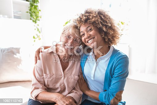 Friendly afro american home nurse embracing senior woman, sitting in living room together and smiling at camera.