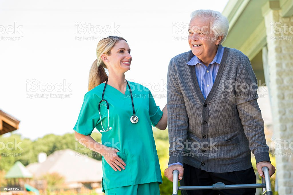 Cheerful home healthcare nurse helps patient walk outdoors stock photo