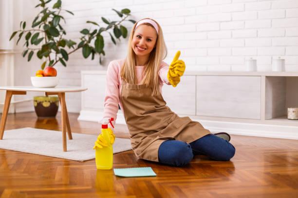 Fröhliche Hausfrau putzt und zeigt Daumen nach oben – Foto
