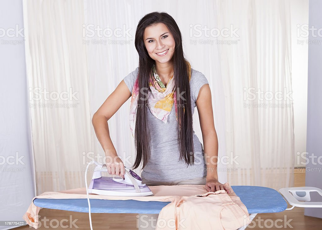 Cheerful housewife ironing the clothes royalty-free stock photo