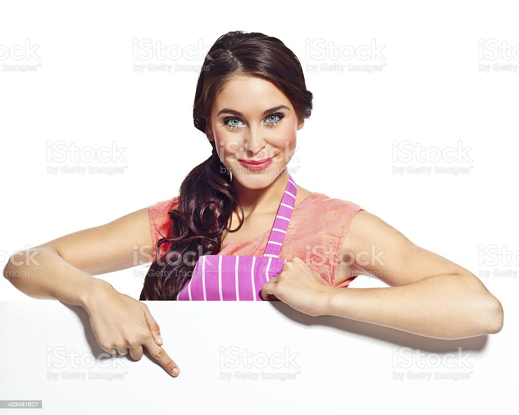 Cheerful housewife with whiteboard Portrait of cheerful young woman wearing an apron pointing at the whiteboard and smiling at the camera. Studio shot, isolated on white. 20-24 Years Stock Photo