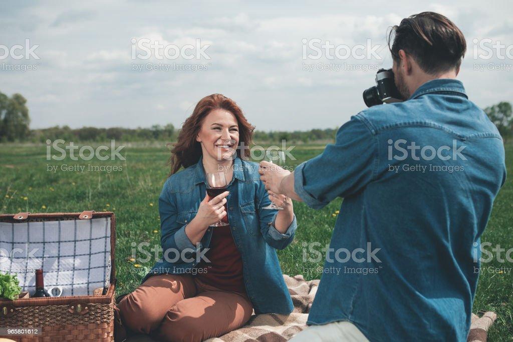Vrolijke man en vrouw hebben romantische picknick op grasland - Royalty-free Activiteit - Bewegen Stockfoto