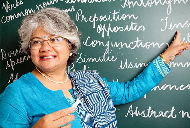freudig indische asiatische frau englisch-lehrer im klassenzimmer mit greenboard - schöne englische wörter stock-fotos und bilder