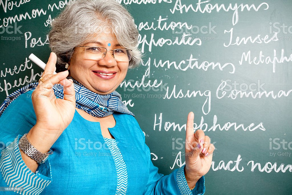 Cheerful Indian Asian Woman English Teacher in Classroom with greenboard stock photo