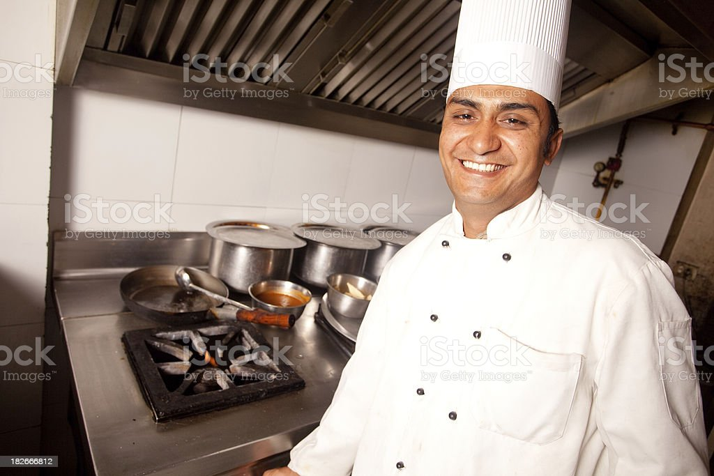 Cheerful Indian Chef working cooking in a Restaurant Kitchen Horizontal stock photo