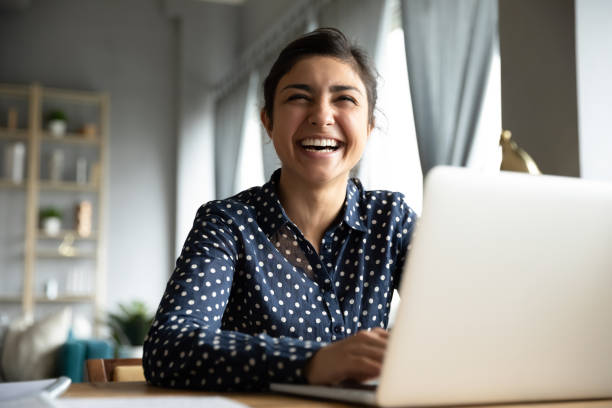 Cheerful indian girl laughing sit with laptop at table Cheerful indian girl student professional laughing looking away sit with laptop computer at home office table, positive hindu woman having fun enjoy sincere emotion laughter studying working on pc student life stock pictures, royalty-free photos & images