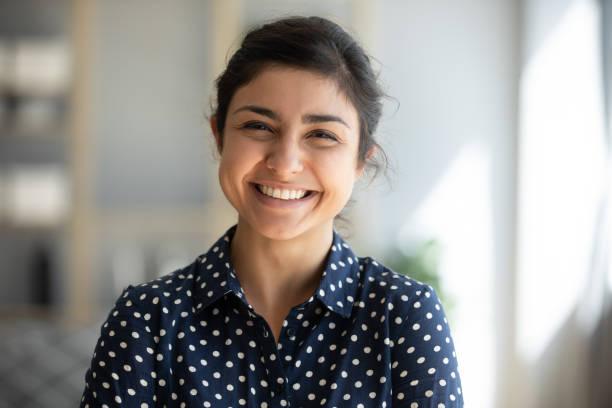 歡快的印度女孩站在家庭辦公室看著相機 - 年輕成年人 個照片及圖片檔