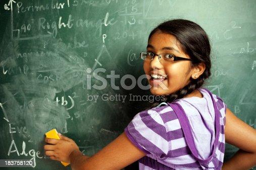 istock Cheerful Indian Girl Student Erasing Mathematics Problems from Greenboard Blackboard 183758120