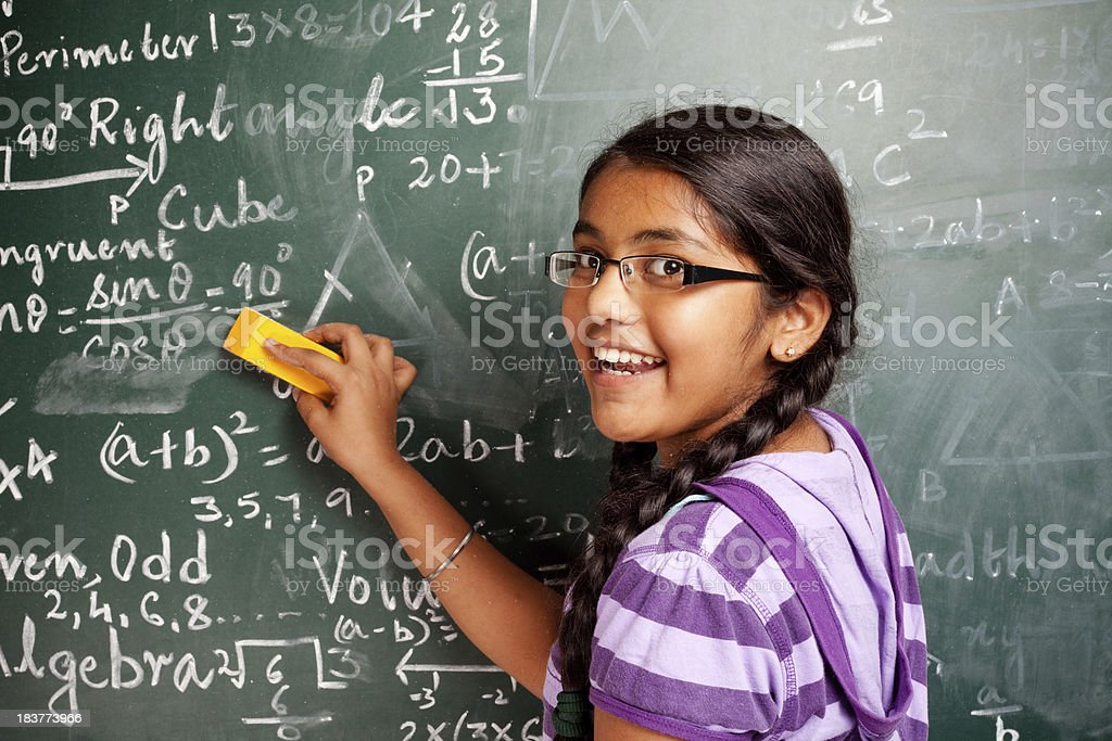 Cheerful Indian Girl Student Erasing Mathematics Problems from Greenboard Blackboard stock photo