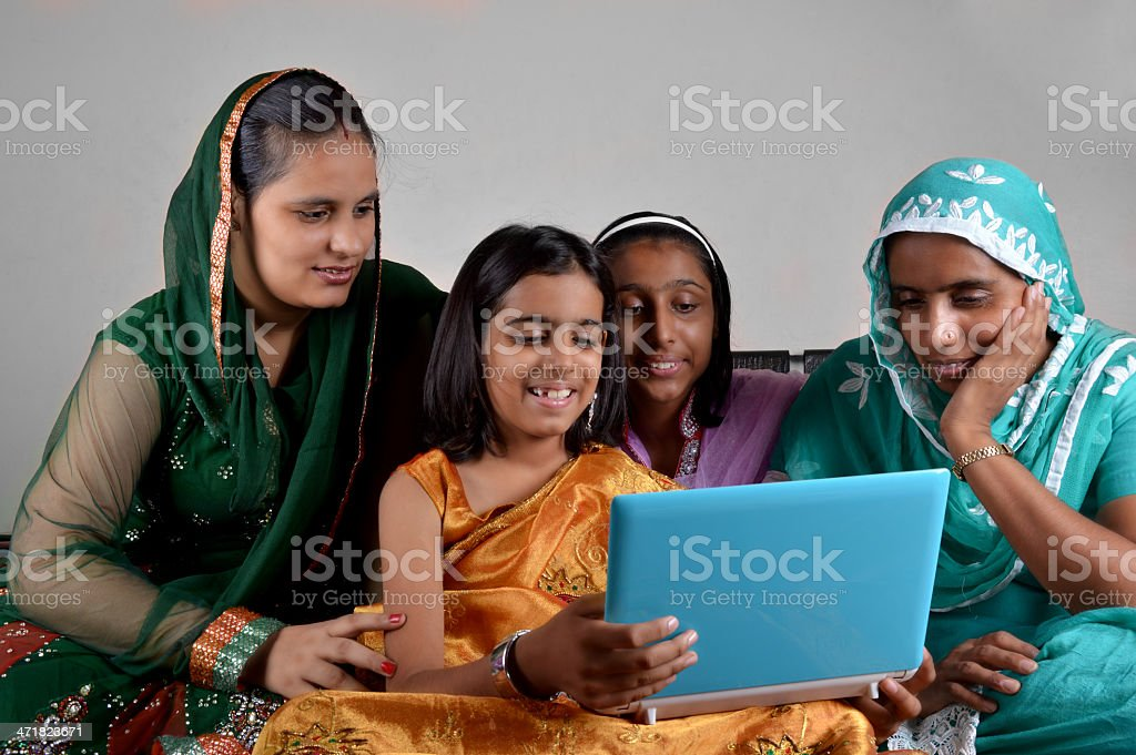 Cheerful Indian Little Girl Holding Laptop with Her Family royalty-free stock photo