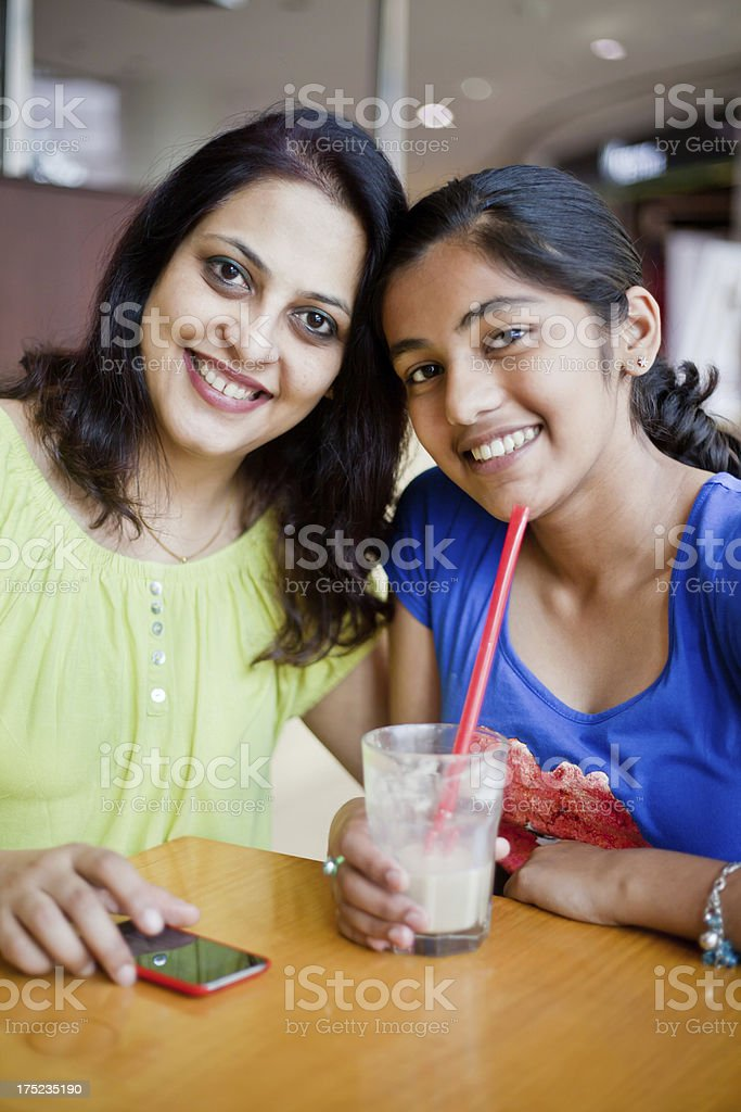 Cheerful Indian Mother and Daughter sitting at Cafeteria royalty-free stock photo