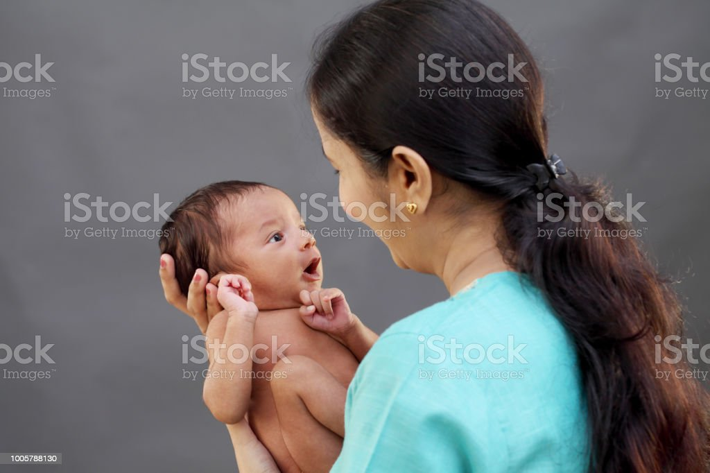 Cheerful Indian Mother Playing With Newborn Baby Stock Photo