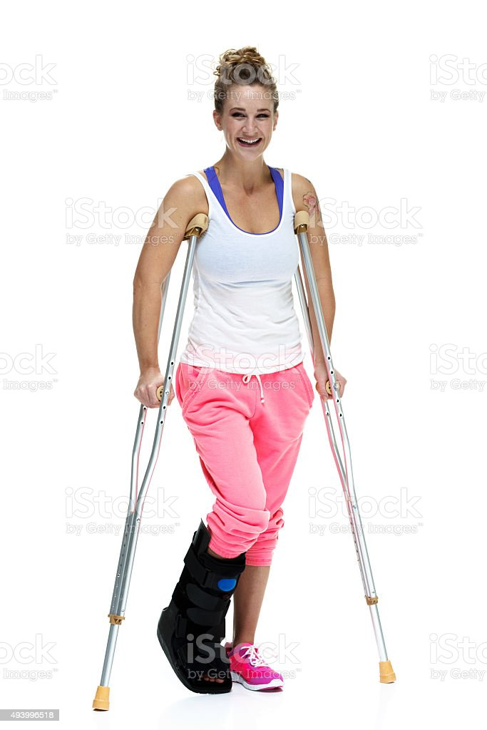 Cheerful injured woman with crutches stock photo