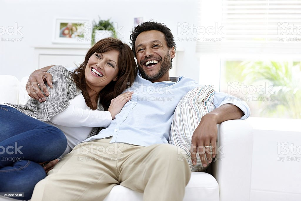 Cheerful interracial couple sitting relaxed on couch at home stock photo