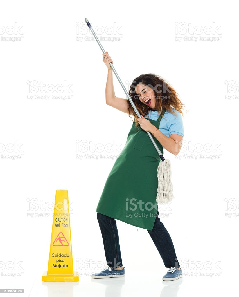 Cheerful janitor cheering with broom stock photo