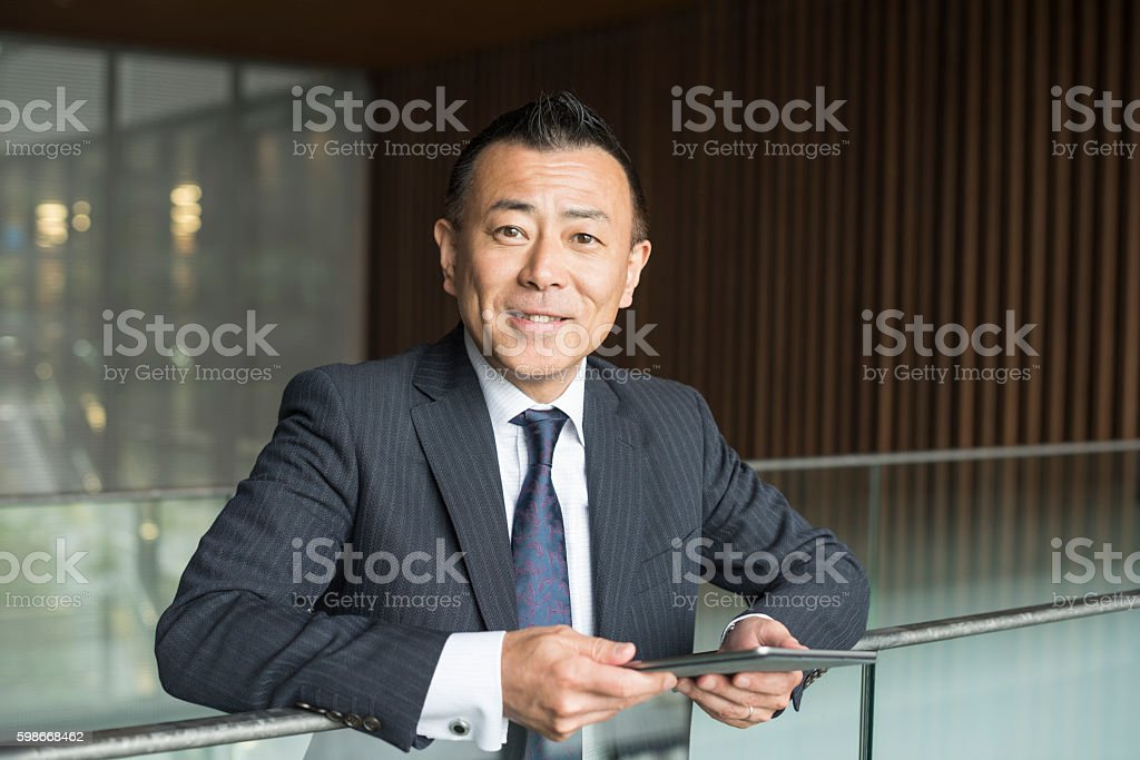 Cheerful Japanese businessman with digital tablet, smiling - foto de stock