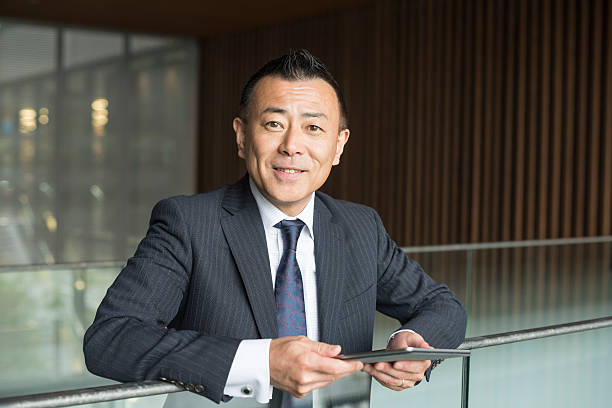 cheerful japanese businessman with digital tablet, smiling - asie photos et images de collection