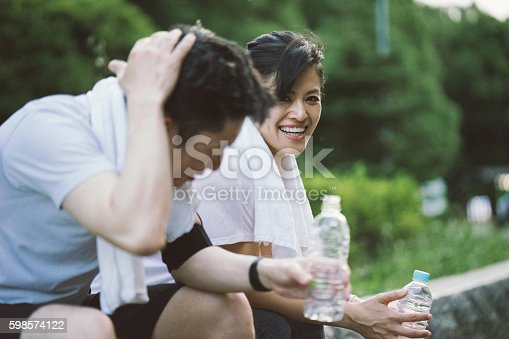 istock Cheerful Japanese couple relaxing after workout in a park 598574122