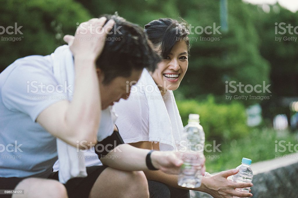 Cheerful Japanese couple relaxing after workout in a park stock photo