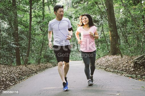 istock Cheerful Japanese couple running outdoors in a park 585586116