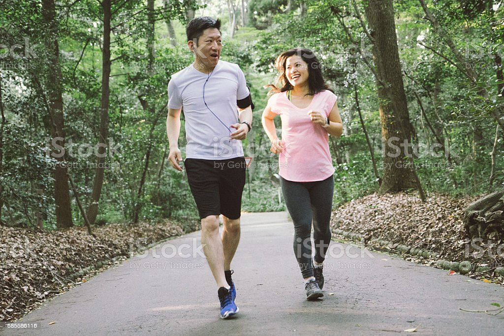 Cheerful Japanese couple running outdoors in a park stock photo